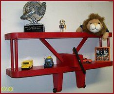 "This little shelf is perfect for an airplane enthusiast. Measures 12"" Wide. Total height is 9"" tall from top of shelf to bottom of wheels. Total depth of shelf is 3.5"". Made in the USA with solid wood and accented with movable wheels and propeller. Made in the USA Red Airplane Shelf Solid Wood Construction Colorful and Bright Features Movable Wheels and Propeller."